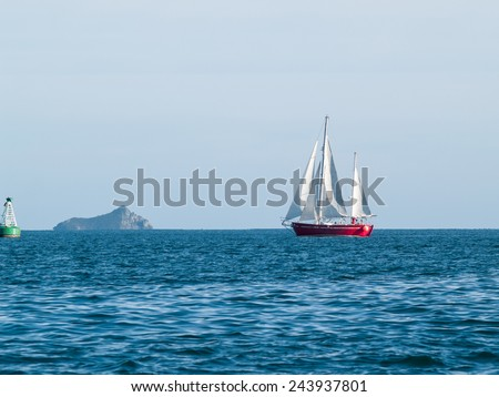 Red ketch yacht heads for the Tauranga harbor, with Karewa Island behind. - stock photo