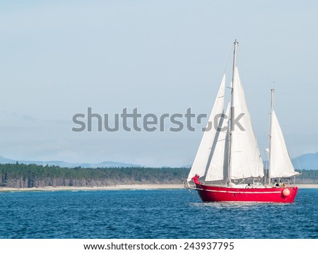 Red ketch yacht heads for the Tauranga harbor, with Matakana Island behind. - stock photo