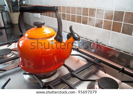 Red kettle on a gas stove - stock photo