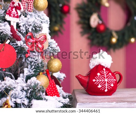Red kettle with tea from a Christmas tree on an old table - stock photo