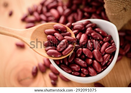 Red Kidney bean in white ceramic bowl and wooden spoon - stock photo