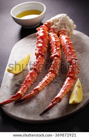 Red king crab legs with lemon on a marble cutting board - stock photo