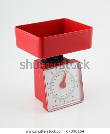 Red kitchen scales on white background - stock photo