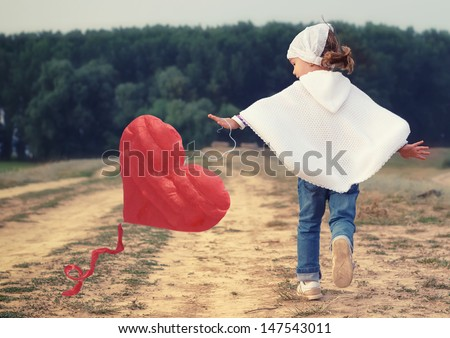 Red Kite with heart shape flying. Lovely little girl playing with red heart kite. - stock photo