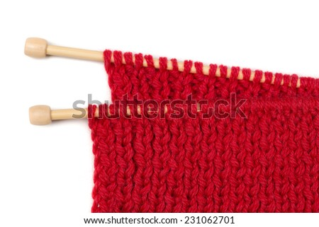 Red knitted wool fabric on wooden spokes. Isolate on white. - stock photo