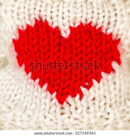 Red knitted wool heart on a white knitted background - stock photo