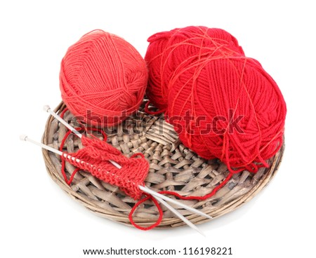 Red knittings yarns on the wicker cradle close-up isolated on white
