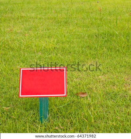 Red label on the green grass. - stock photo