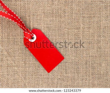 red label with ribbon on burlap background - stock photo