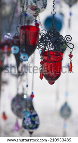 Red lamp in foreground with lamps and charms blurred in background - stock photo