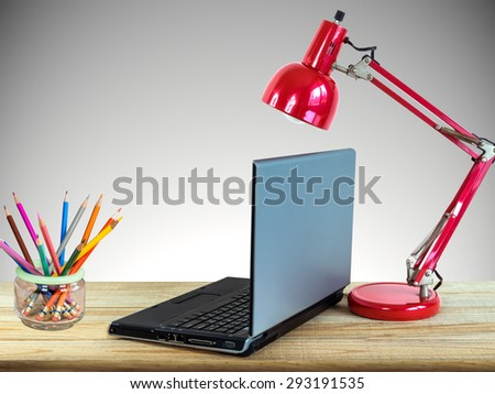 Red lamp, laptop computer, color pencils on wooden table top over grey wall background/ interior still life - stock photo