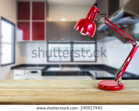 Red lamp on wooden counter top with modern kitchen blurry background - stock photo