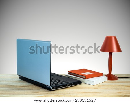 Red lamp with laptop computer, books on wooden table top over grey wall background/ interior still life - stock photo
