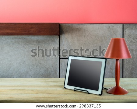 Red lamp with tablet computer on wooden table top over modern wall background/ interior still life - stock photo