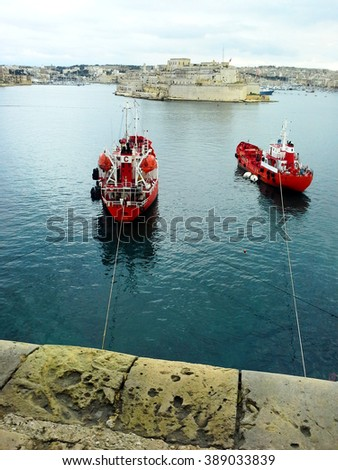 red large ships at the dock near the shore of Malta the city of Valletta at the background of stone walls and ancient historic castle blue sky