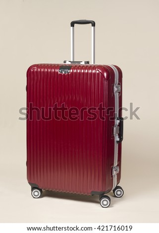 Red large trolley suitcase with silver handle on beige background - stock photo
