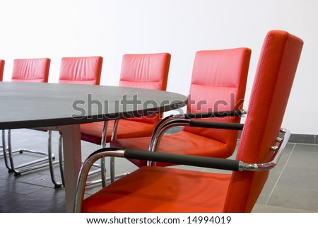 Red leather armchairs in a meeting room - stock photo