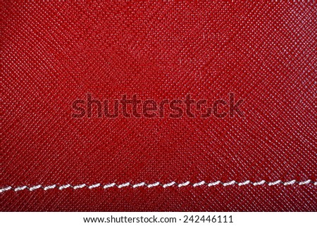 Red leather background with white stitch close up - stock photo