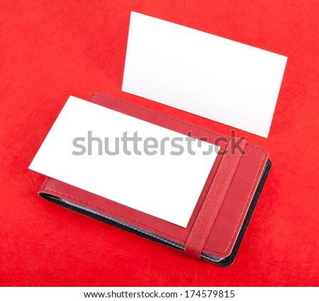 Red leather business cards holder and  blank business cards on red background - stock photo