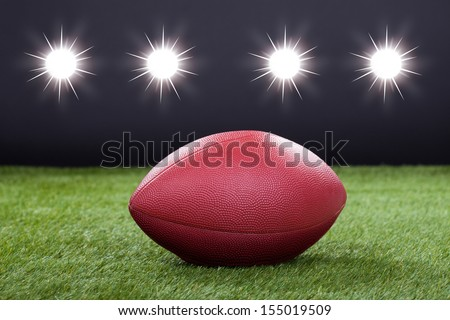 Red Leather Rugby Ball On Pitch Field - stock photo