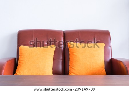 red leather sofa with orange pillow - stock photo