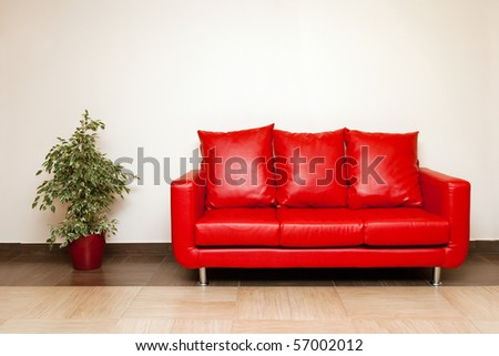 Red leather sofa with pillow, plant in a pot near - stock photo