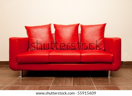 Red leather sofa with pillow. Red Divan - stock photo