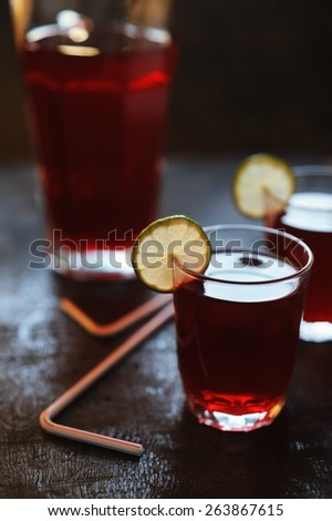 Red lemonade with lime slices - stock photo