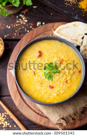 Red lentil Indian soup with flat bread on a wooden background. Masoor dal.  - stock photo