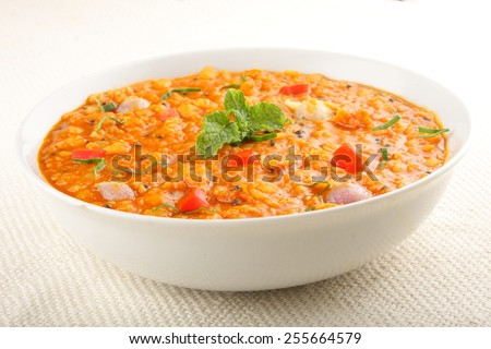 Red lentil soup with tomato and fresh herbs with selective focus. - stock photo