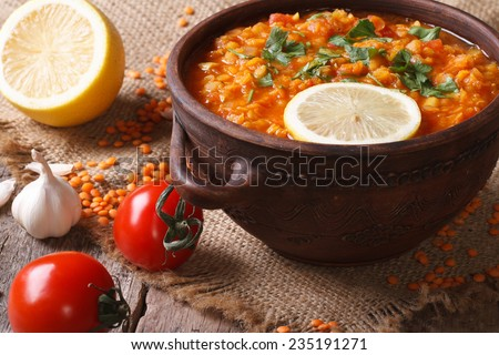 Red lentil soup with vegetables close-up on the table. horizontal, rustic style