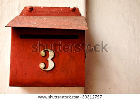 Red letterbox on cream wall, number 3. - stock photo