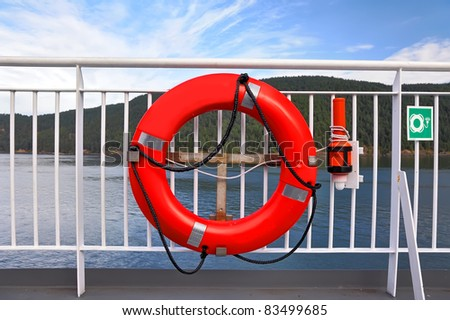 Red life buoy and alarm buoy by the ship