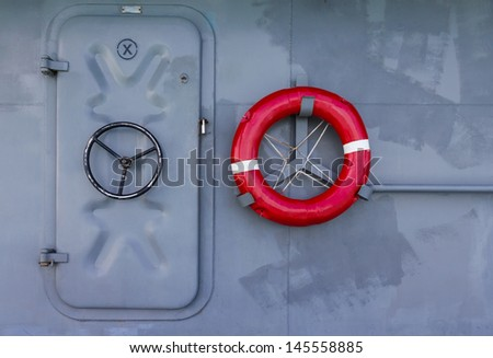 Red life buoy and metal door on warship