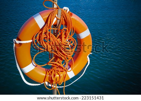 red life buoy hanging above the  water - stock photo
