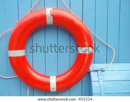 Red lifebuoy hanging on a clear blue wall - stock photo