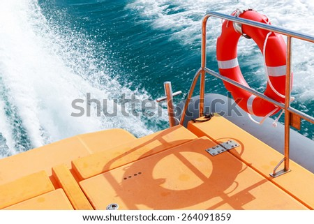 Red lifebuoy hanging on steel railings of safety rescue boat - stock photo