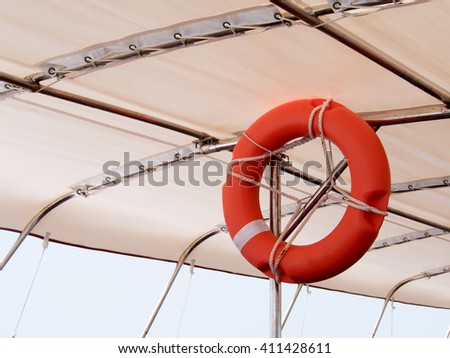 Red lifebuoy, life preserver hanging on roof of boat for fast safety rescue boat. Life Buoy on a Cruise Ship. - stock photo