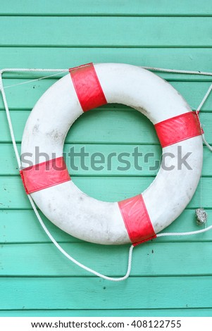 red lifebuoy on a green wooden plank wall, summer concept, background - stock photo