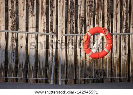 Red lifebuoy with rope on metal railings above weathered wooden wall in port - stock photo