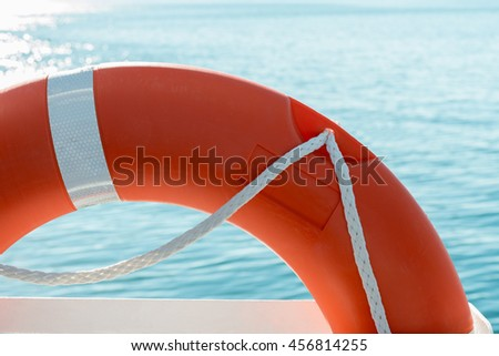 red lifesaver on a boat and sea background - stock photo