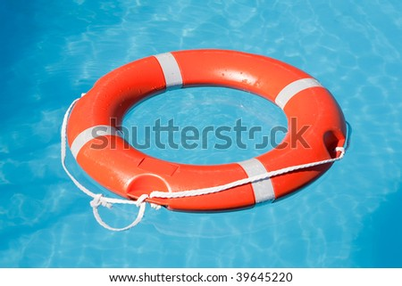 Red lifesaving float on blue water - stock photo