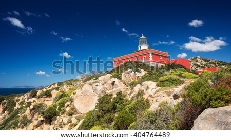 Red light house above the Mediterranan coast in a sunny day - stock photo