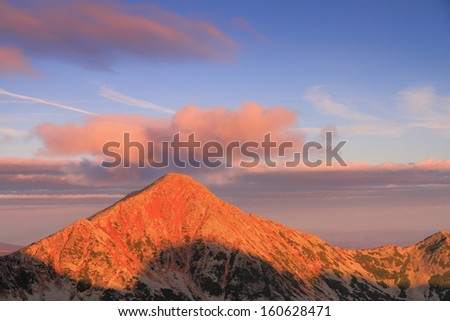 Red light over the mountains at sunrise - stock photo