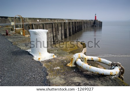 red lighthouse at the end of wharf, Watchet, Somerset, England.  Great depth of field. - stock photo