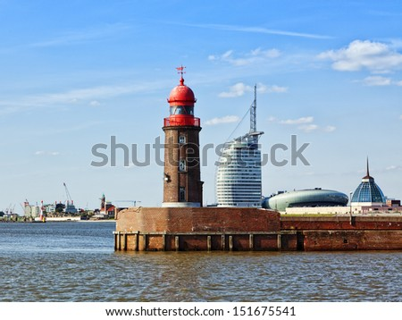 red lighthouse at the harbor entrance of Bremerhaven, modern buildings in background - stock photo