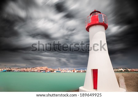 Red lighthouse in the enter of the harbor - stock photo