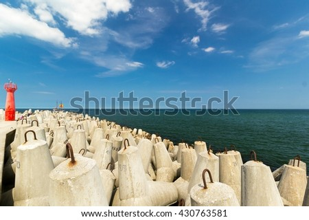 Red lighthouse next to the breakwater, Baltic Sea, Poland - stock photo
