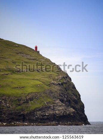 Red lighthouse on a cliff looking over the ocean - stock photo