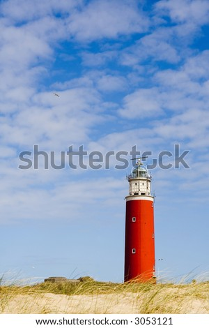 Red lighthouse on dunes.